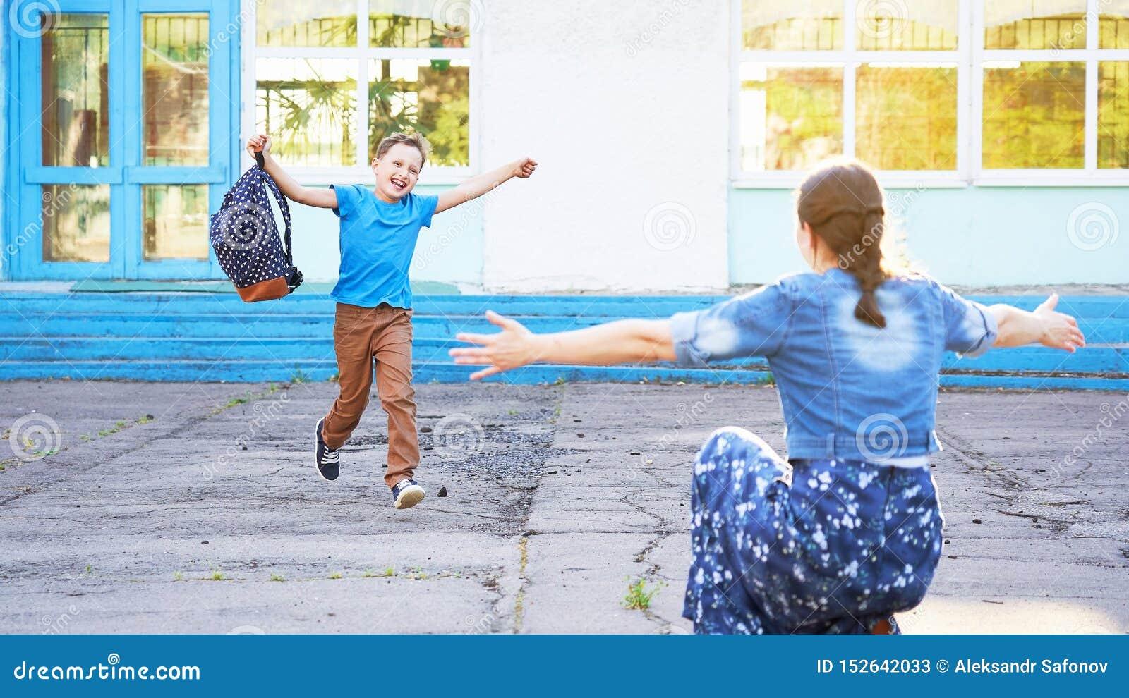 Mama spotyka jej syna od szkoły podstawowej radosny dziecko biega w ręki jego matka szczęśliwy uczeń biega w kierunku jego matki