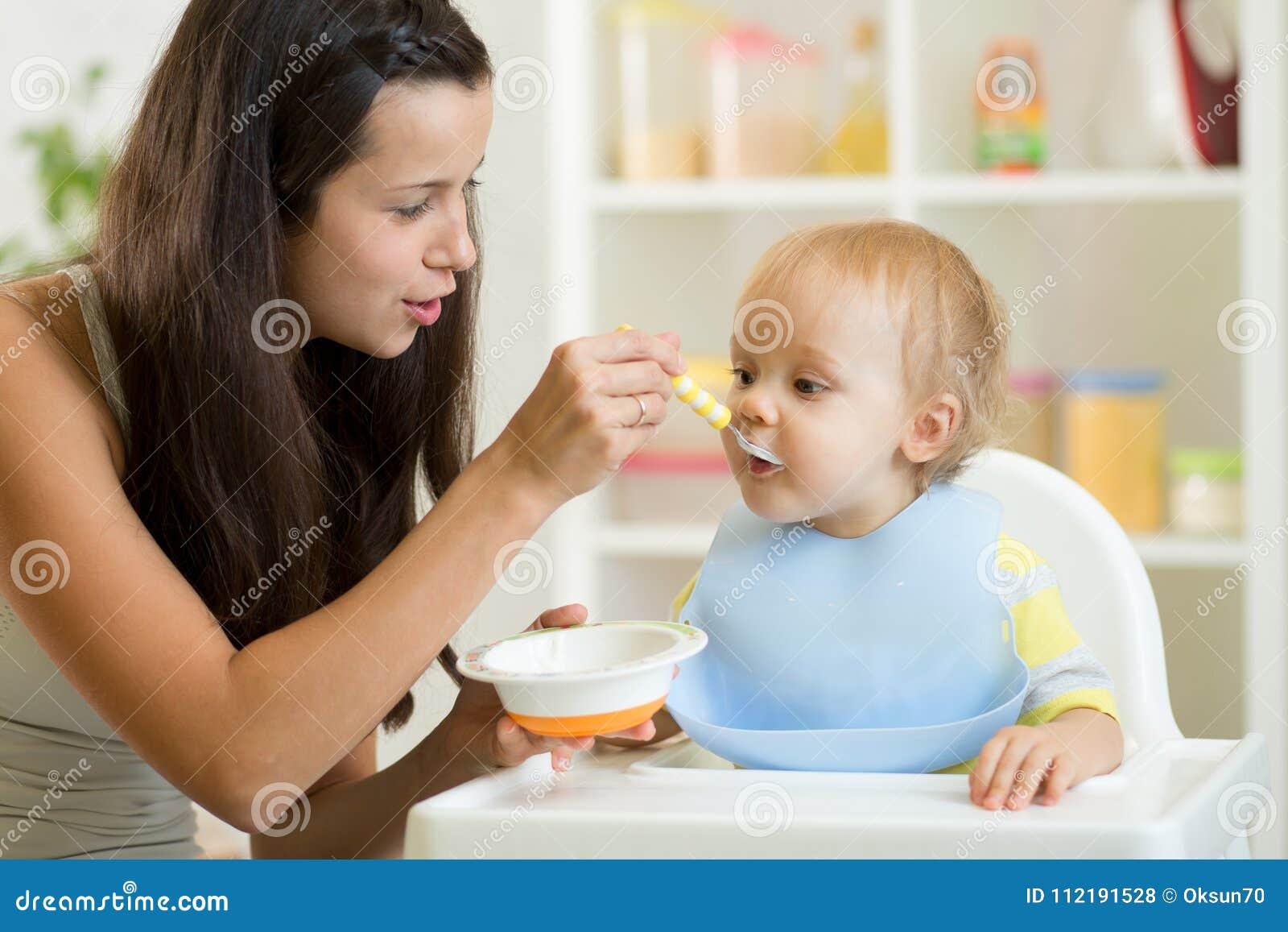 Maman alimentant le bébé affamé dans le highchair à l intérieur