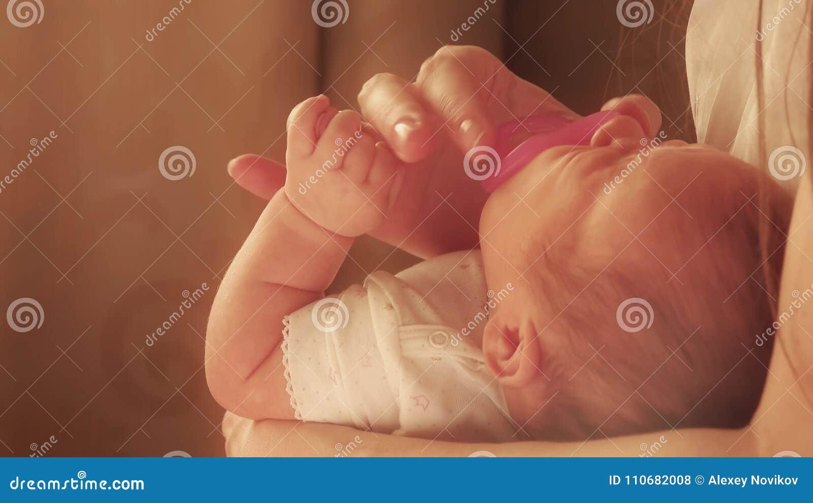 Maman calmant son bébé nouveau-né tatillon avec la tétine rose