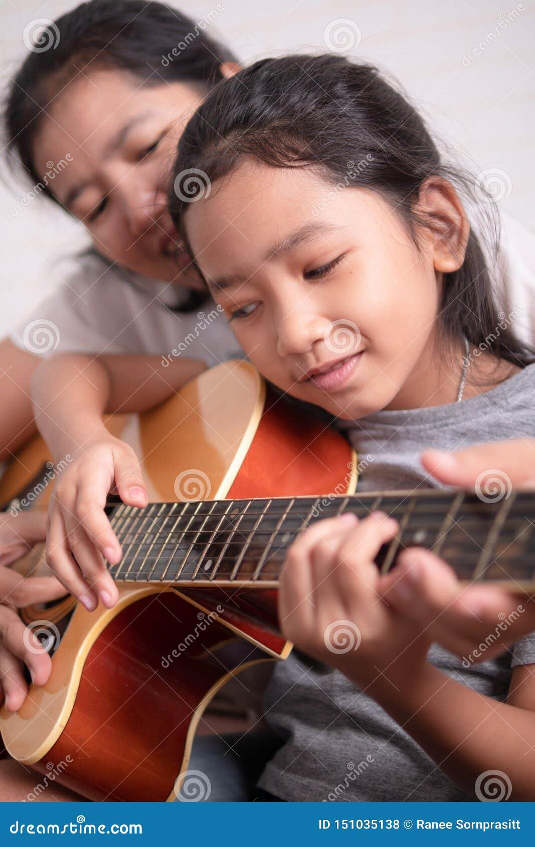 Maman enseignant sa fille à jouer la guitare