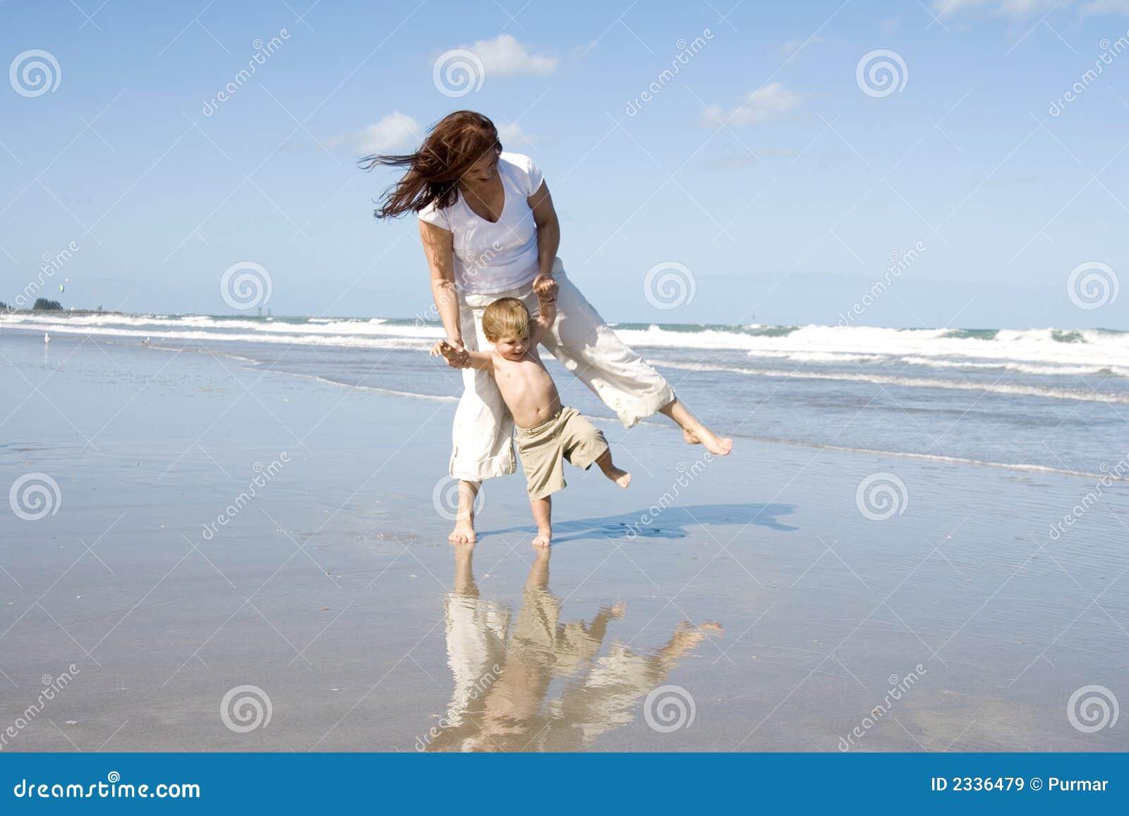 Maman et fils marchant sur une plage