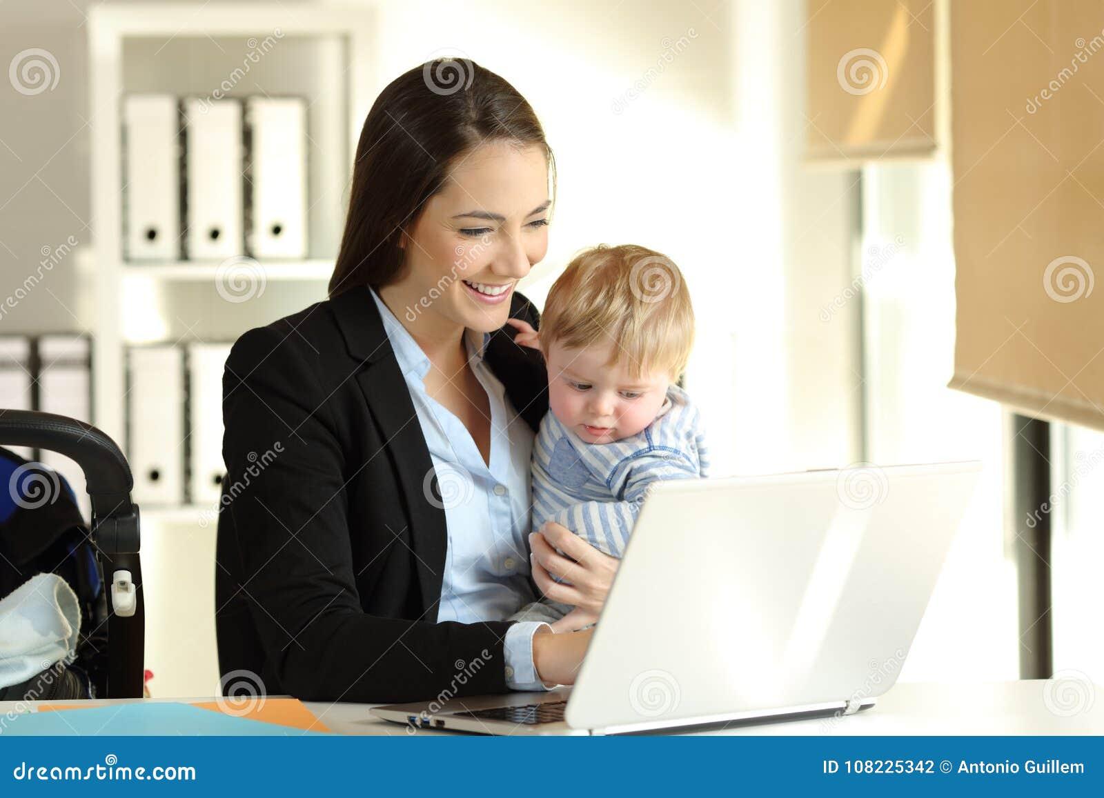 Maman travaillant avec son fils de bébé au bureau photo stock