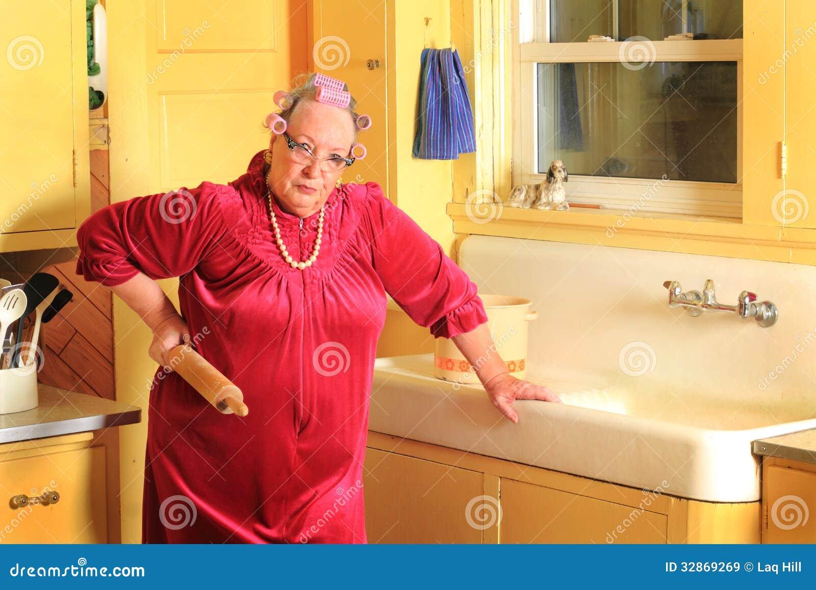 Mamie supérieure grincheuse avec le stylo de roulement