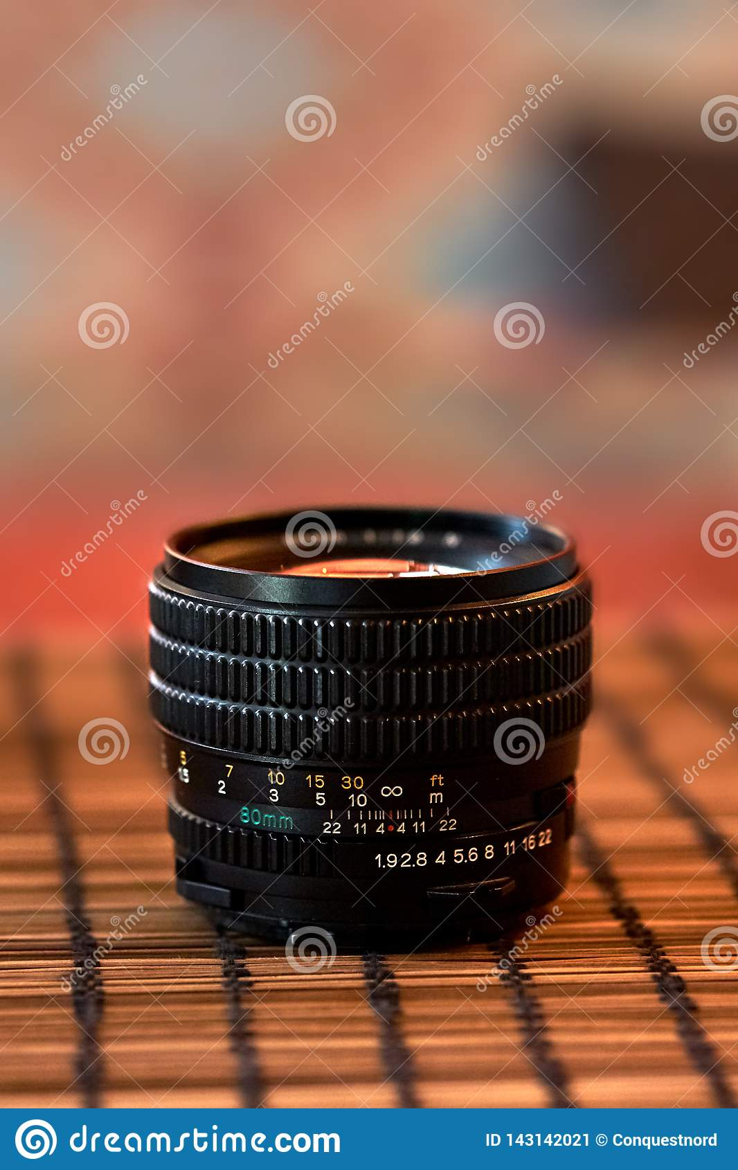 Mamiya lens is on the table on a blurred background.