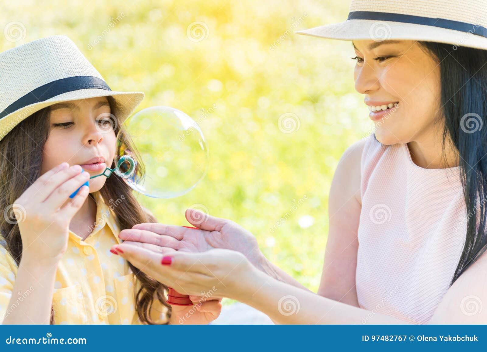 Mamma allegra e figlia che giocano sul pascolo