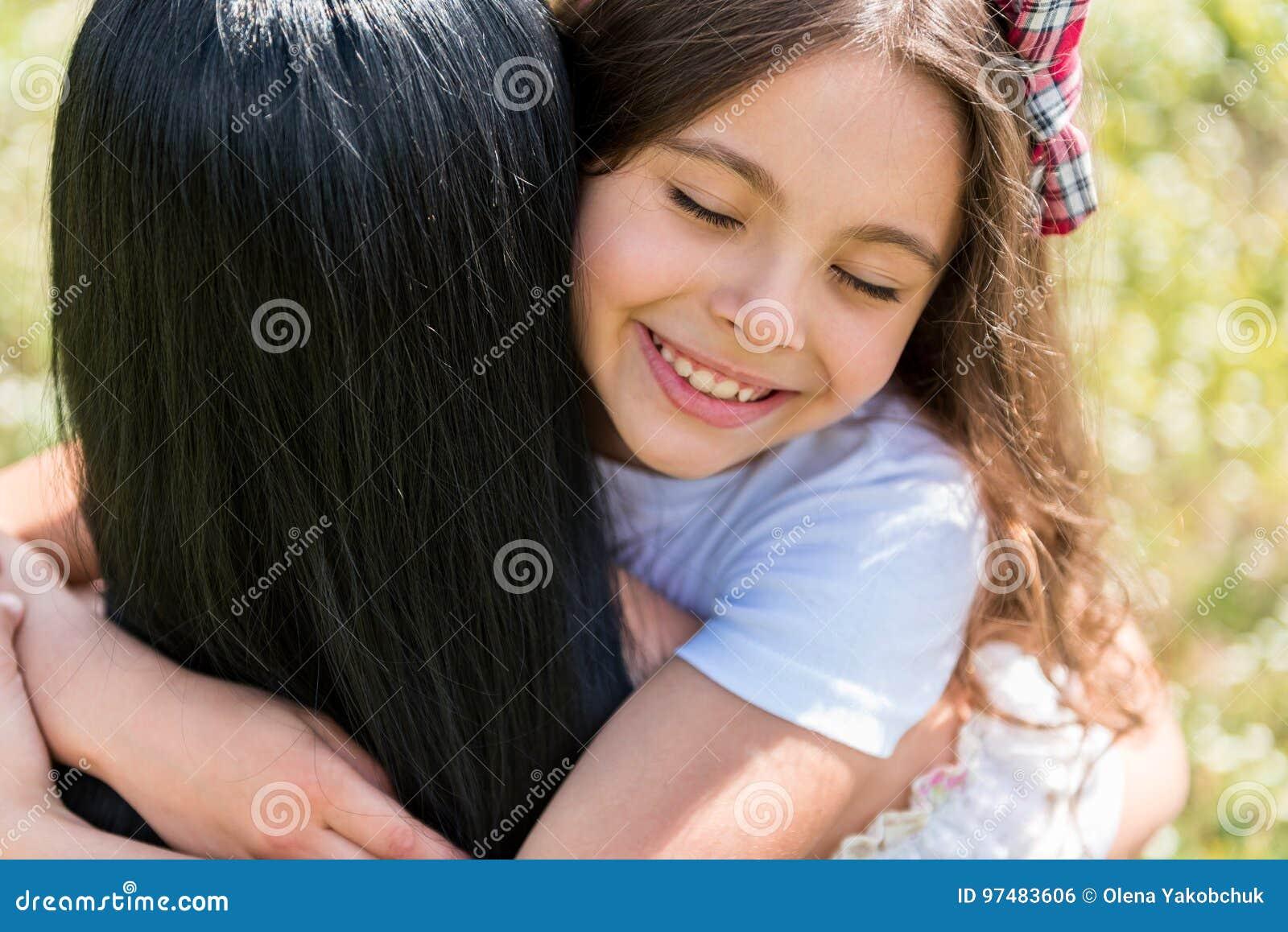 Mamma d abbraccio della ragazza allegra sul prato