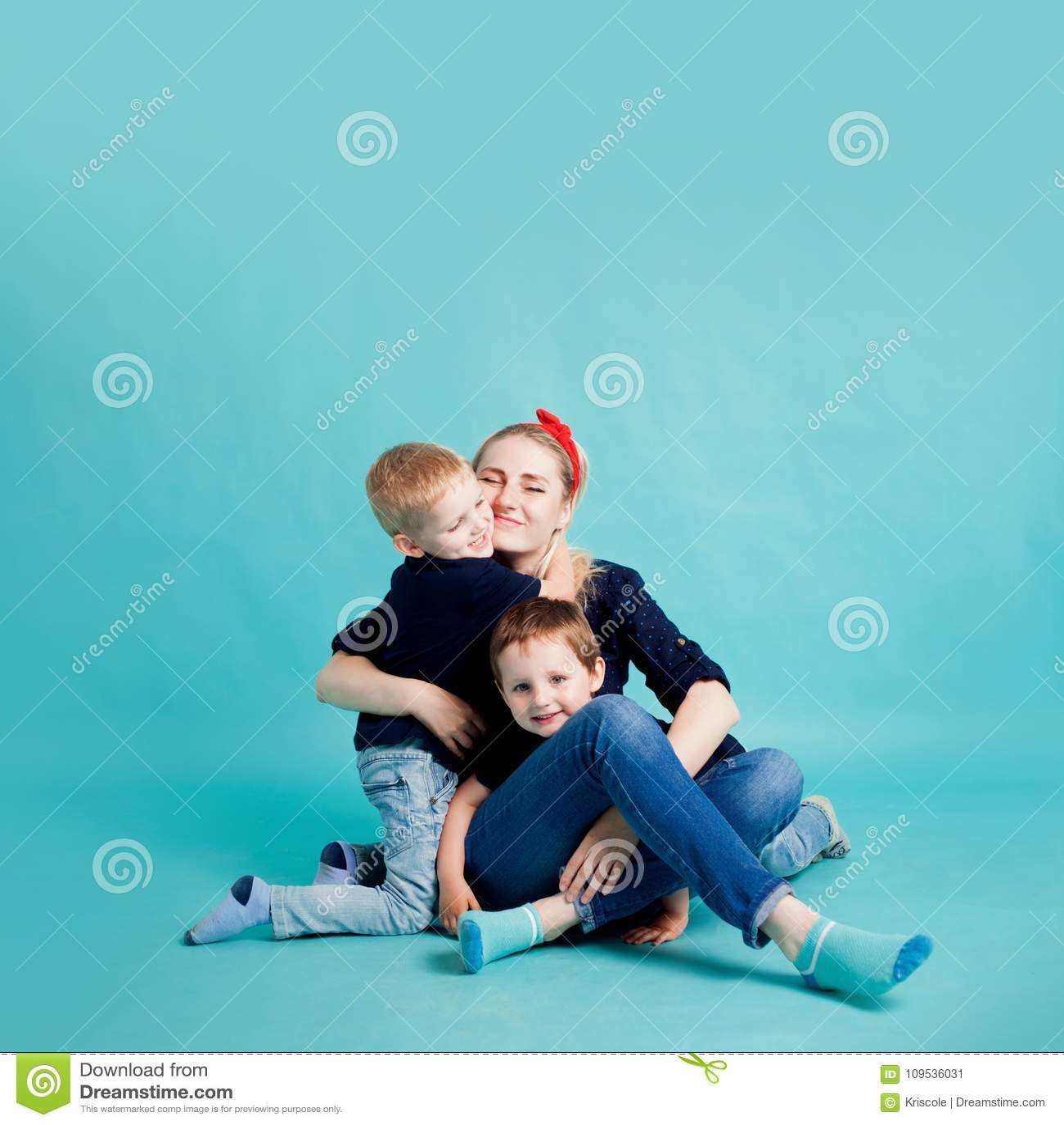 Mamma e figli, ritratto su fondo blu hug
