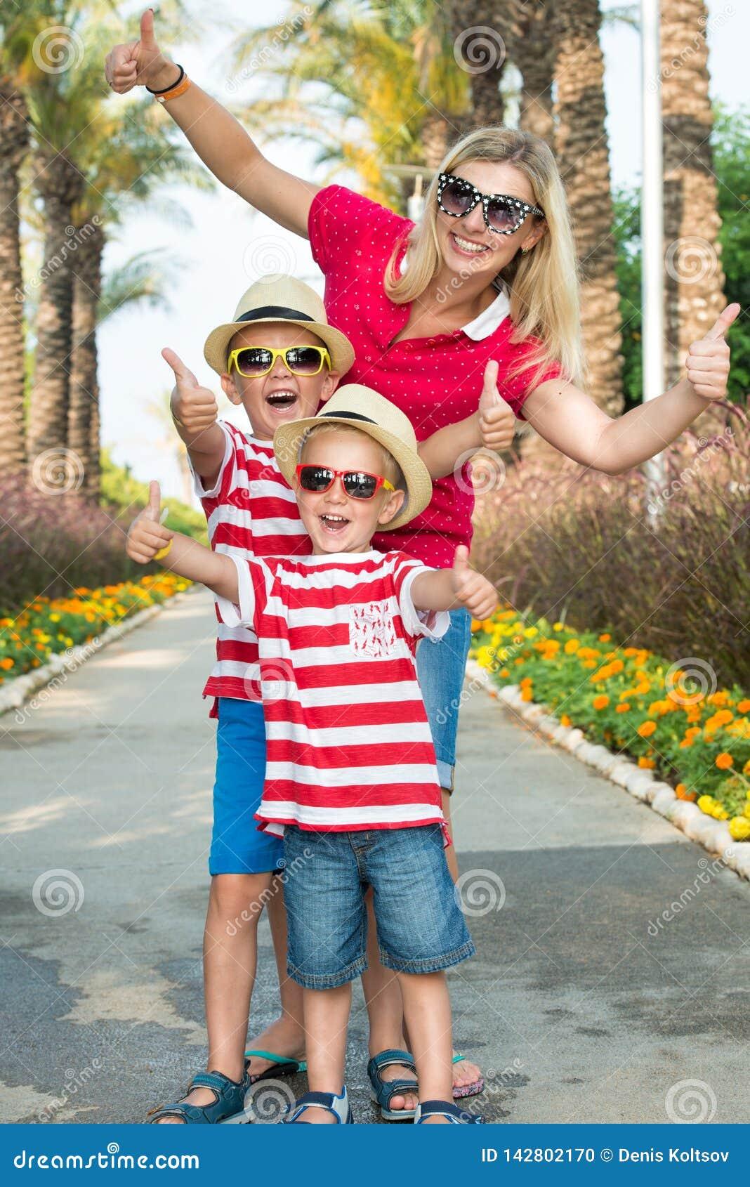 Mamma e figlio due in occhiali da sole e cappelli da camminare tramite il vicolo delle palme Vacanze estive della famiglia
