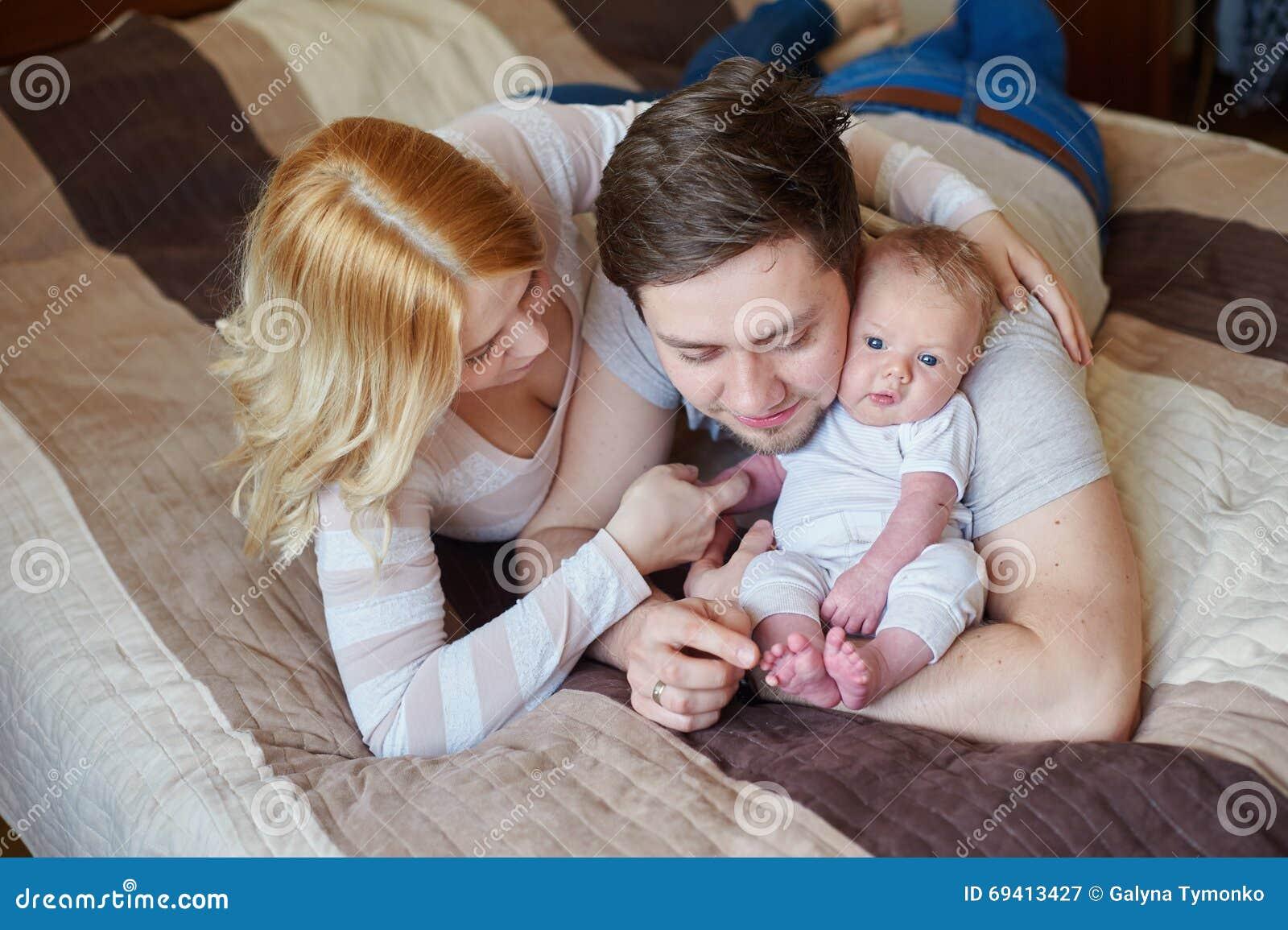 Popolare Mamma E Papà Che Giocano Con Suo Figlio Del Bambino Sul Letto  BY13