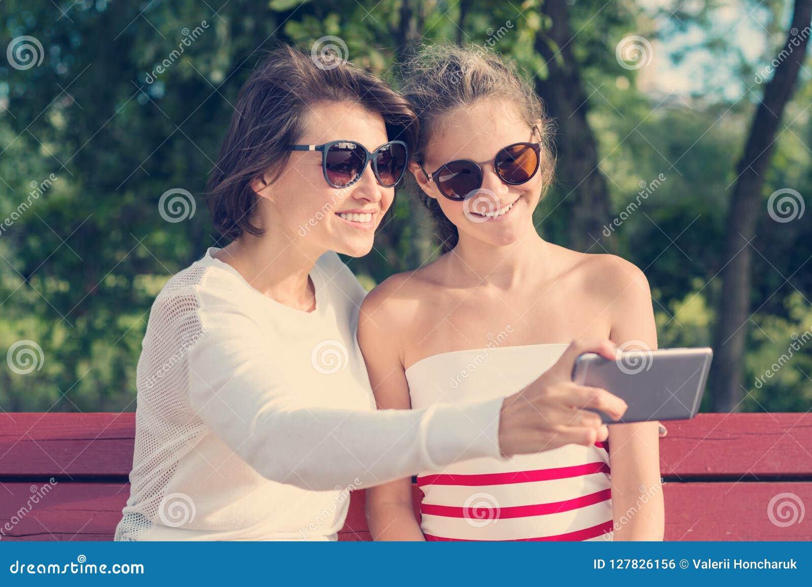 Mamma en dochter, verhouding tussen ouder en tiener, openluchtportret die van moeder met meisje die pret hebben, foto s op mobi n