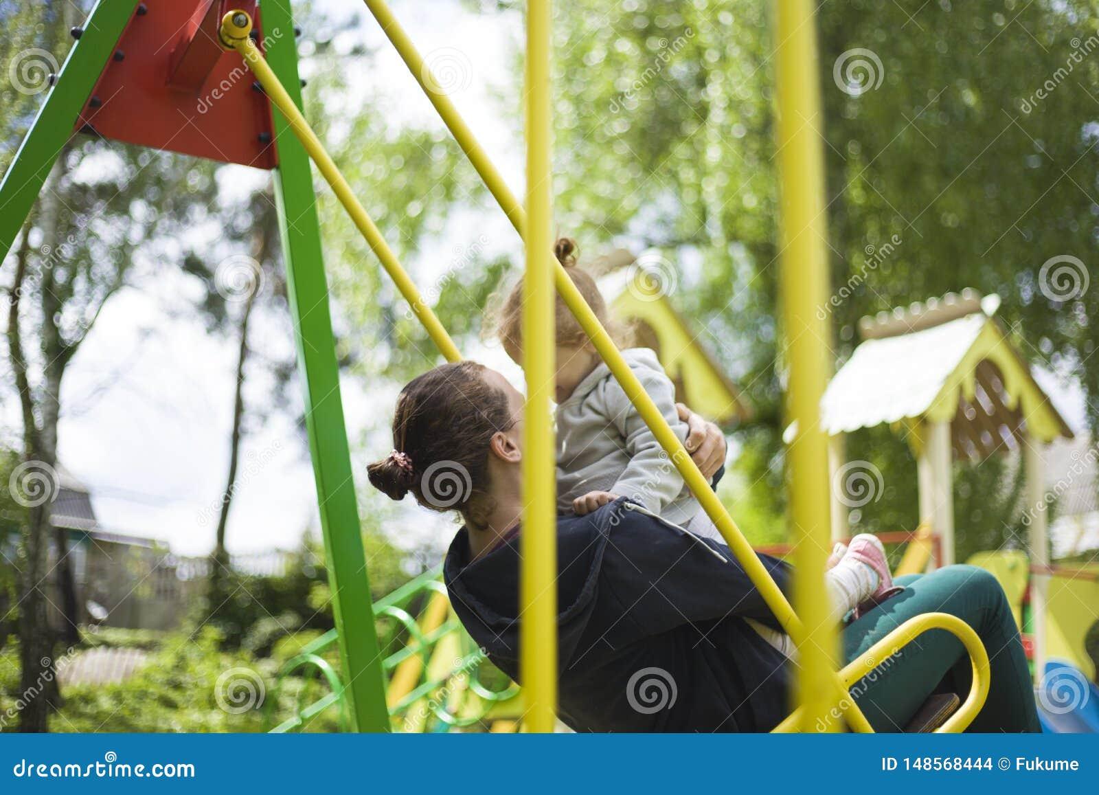 Mamma en dochterrit op een schommeling in een kinderenpark de moeder rolt een klein meisje op een schommeling