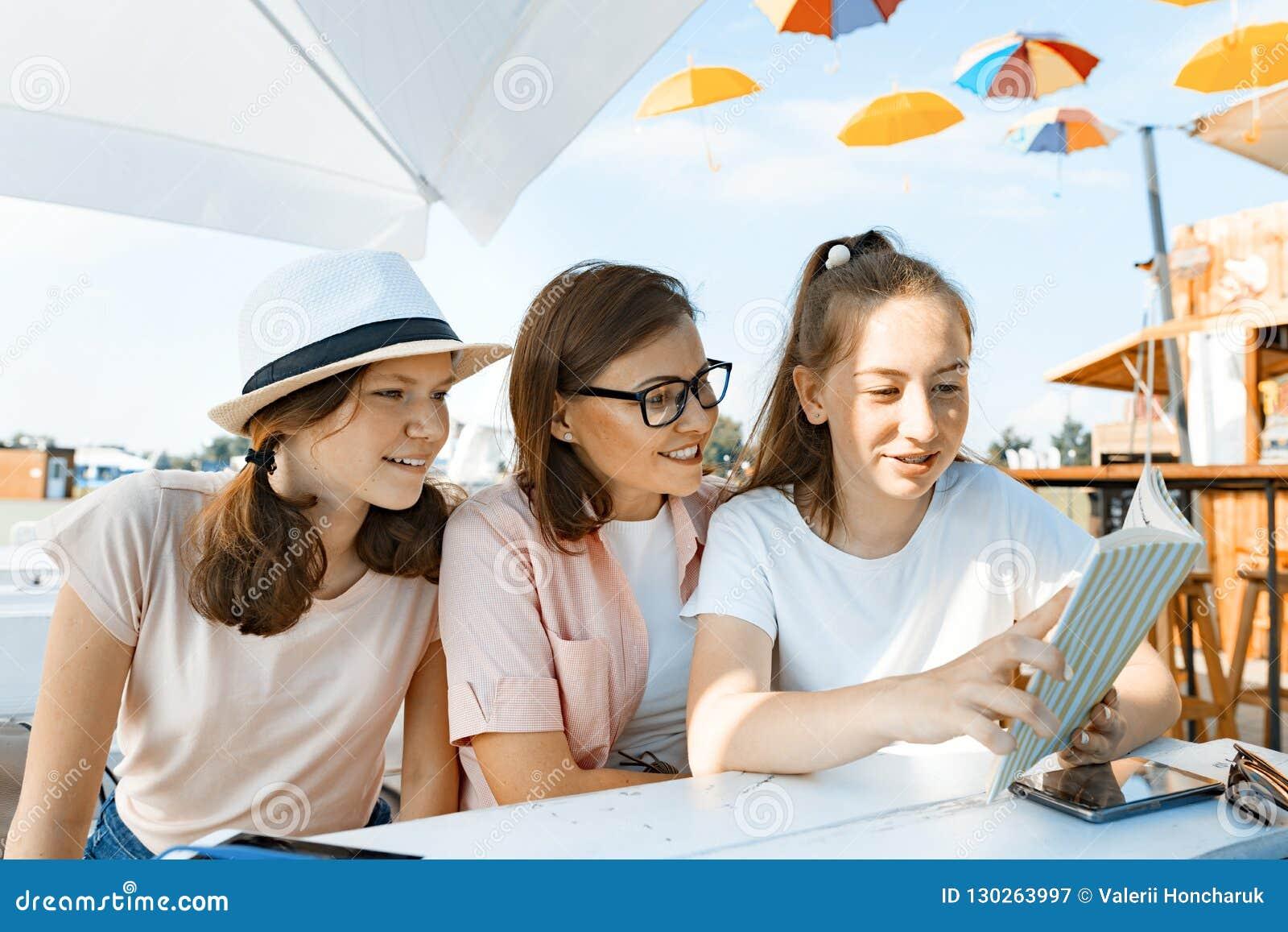 Mamma en dochters de tieners hebben pret, sprekend, kijken en lezen grappig boek Mededeling van de ouder en de kinderen van adole