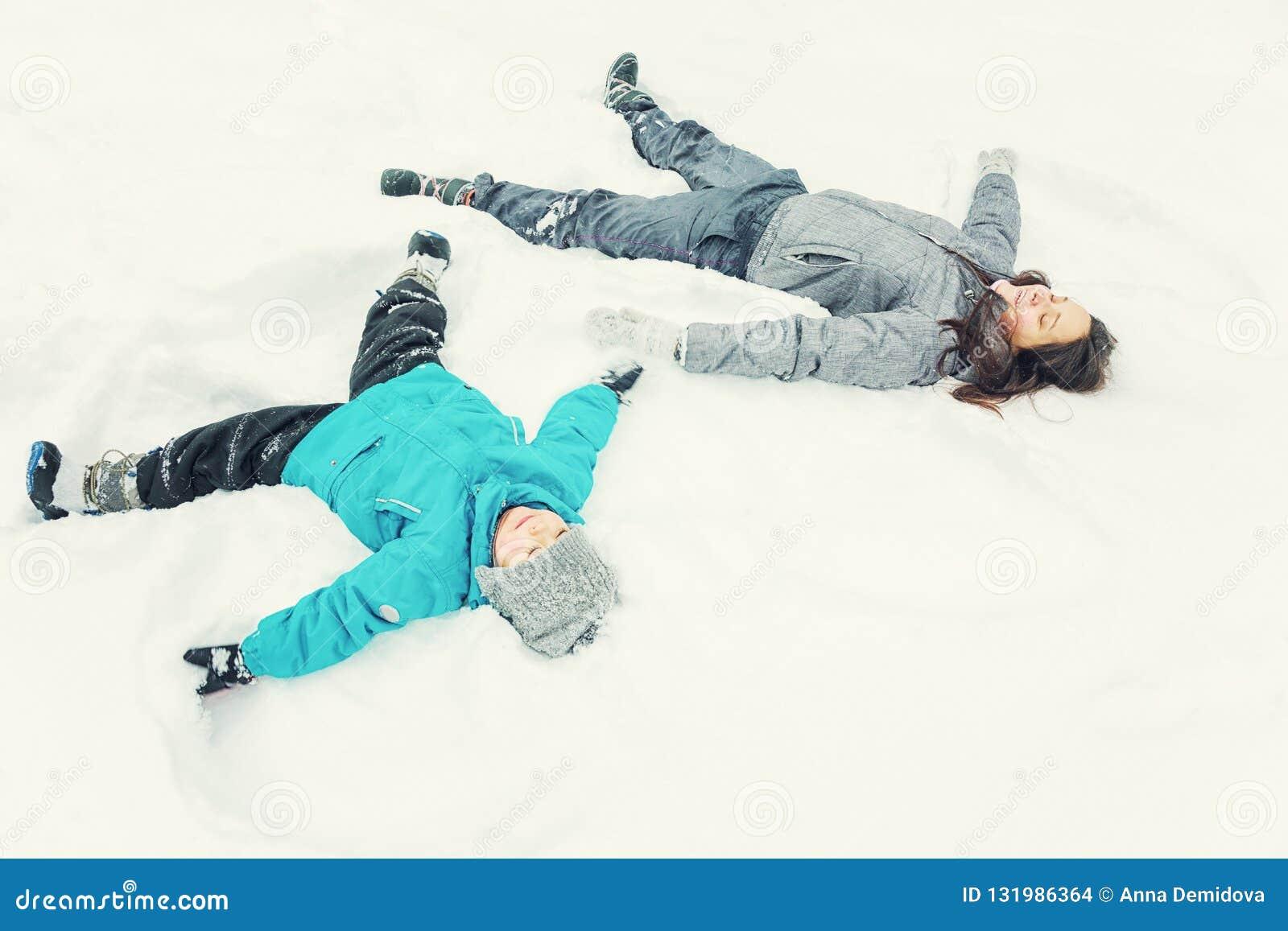 Mamma en weinig zoon die in de sneeuw spelen