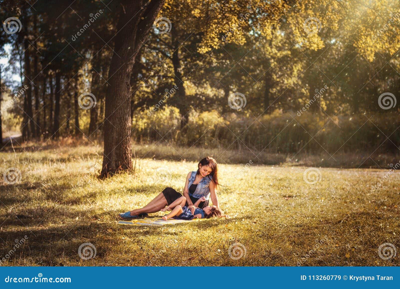 Mamma med ett barn på en gå i den felika skogen