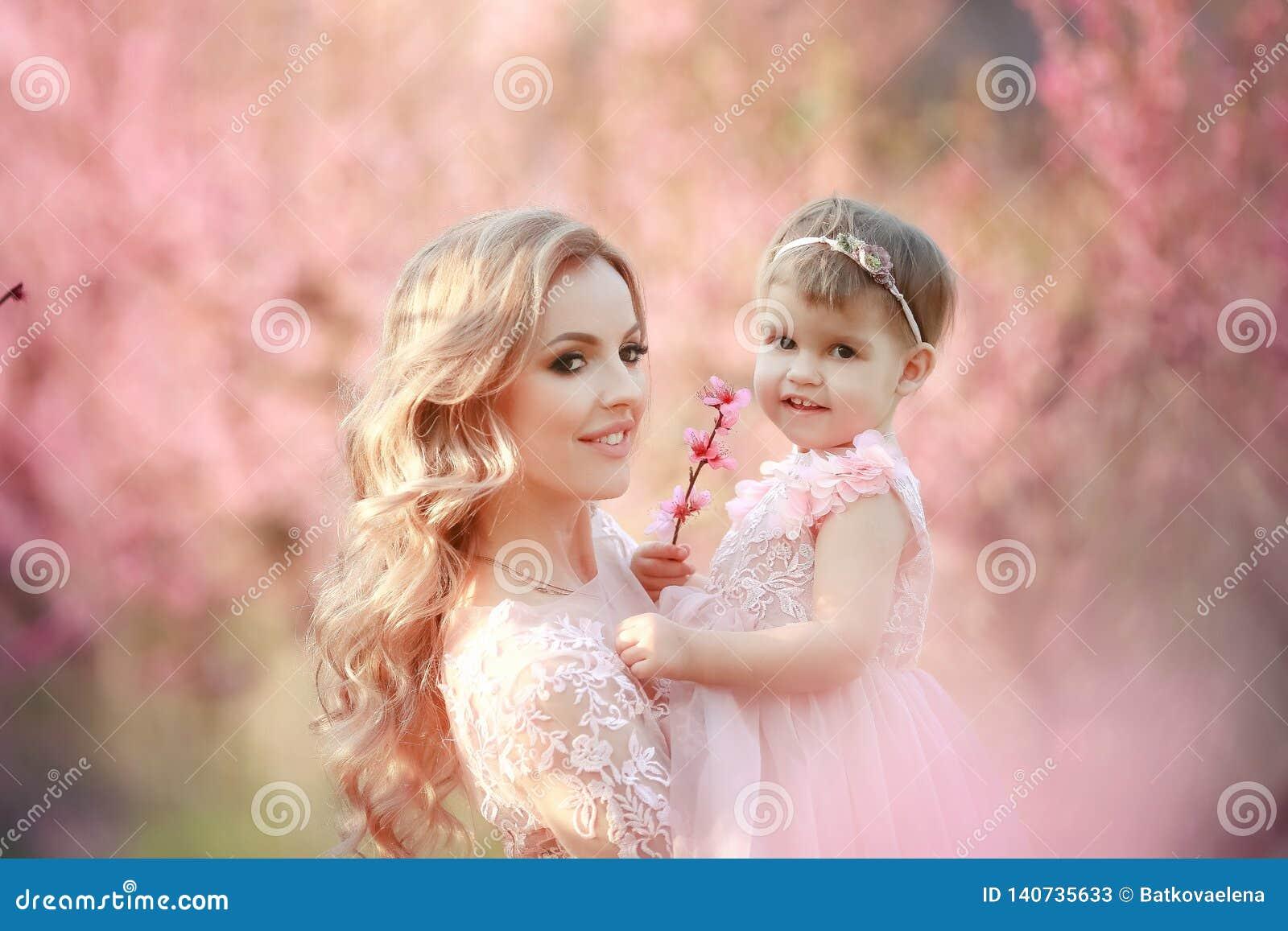 Mamma met een zuigeling in de roze tuin met bloemenbomen