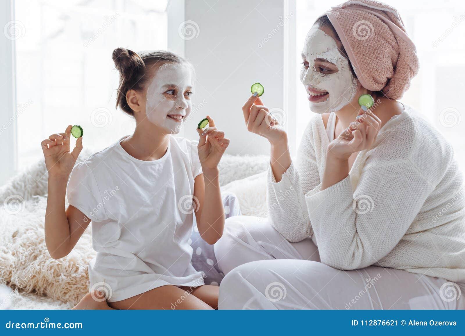 Mamma met haar dochter die het masker van het kleigezicht maken
