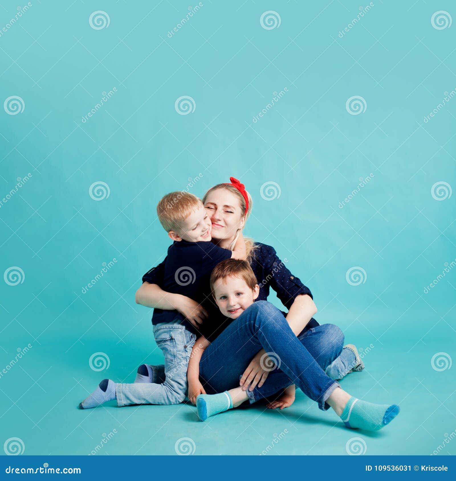 Mamma och söner, stående på blå bakgrund kram