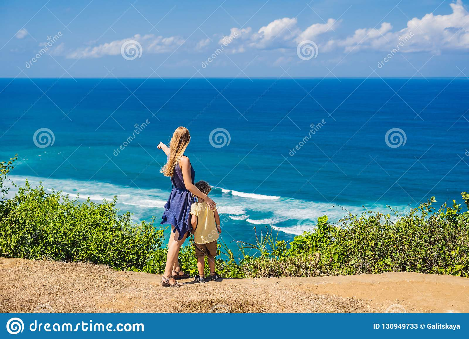Mamma- och sonhandelsresande på en klippa ovanför stranden Tomt paradis