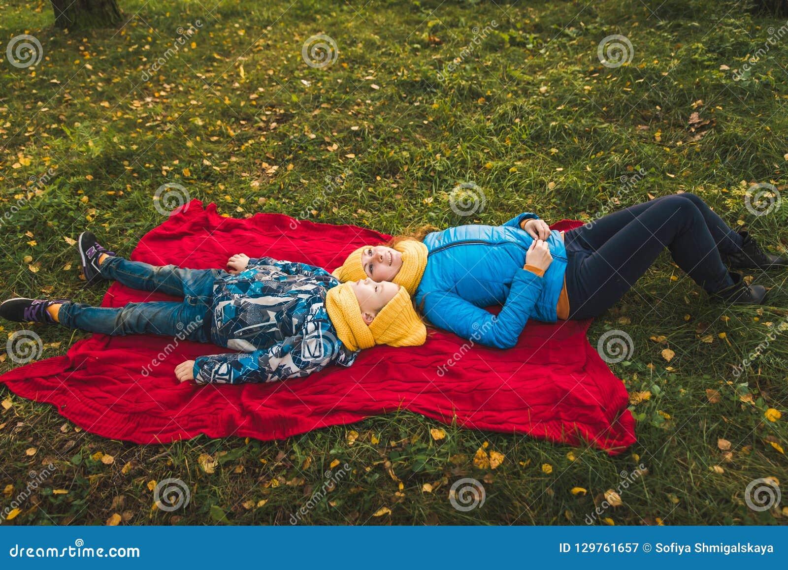 Mamma- och sonlögn på en filt på gräset