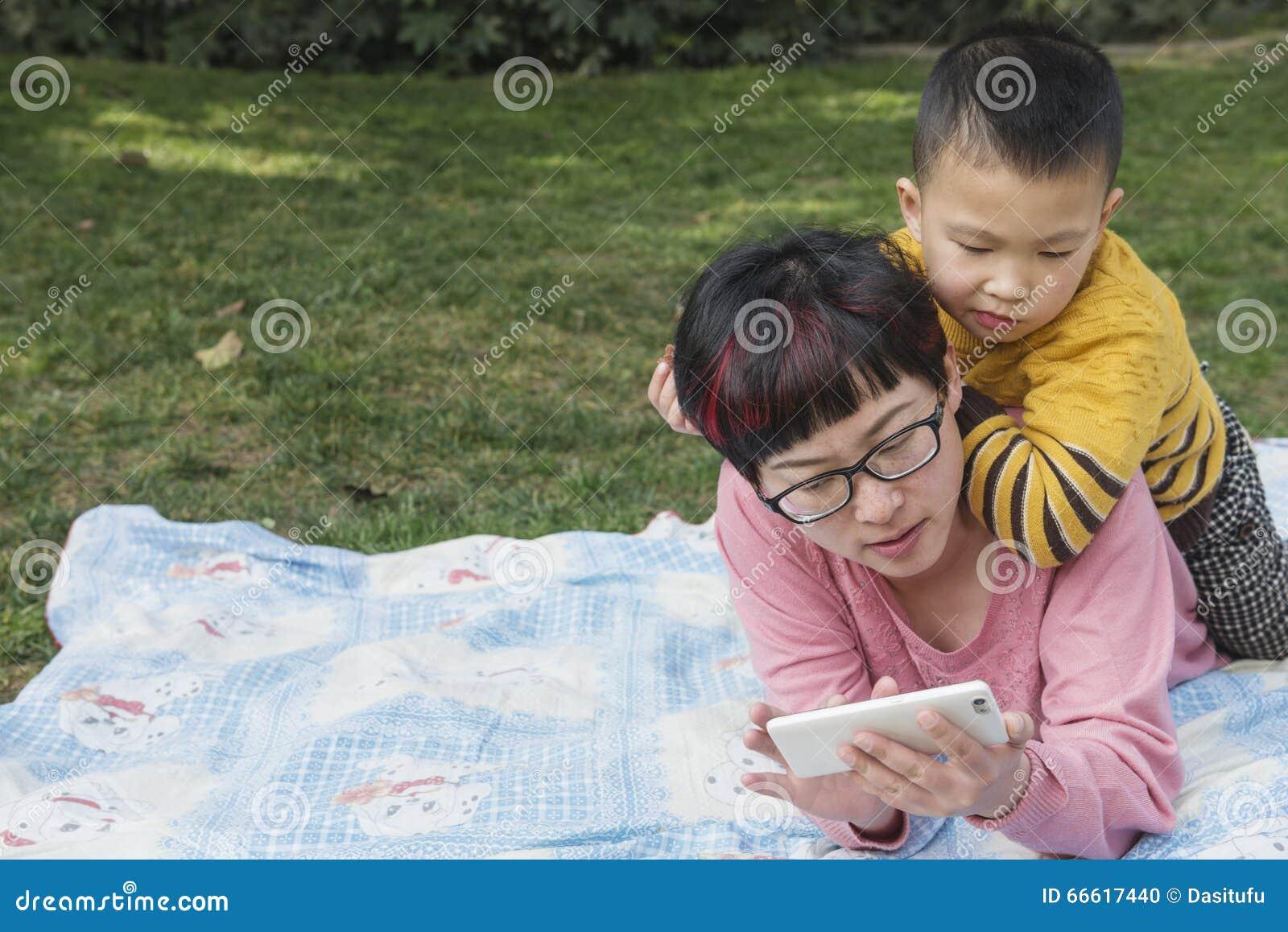 Mamma som använder smartphonen med att hålla ögonen på för unge