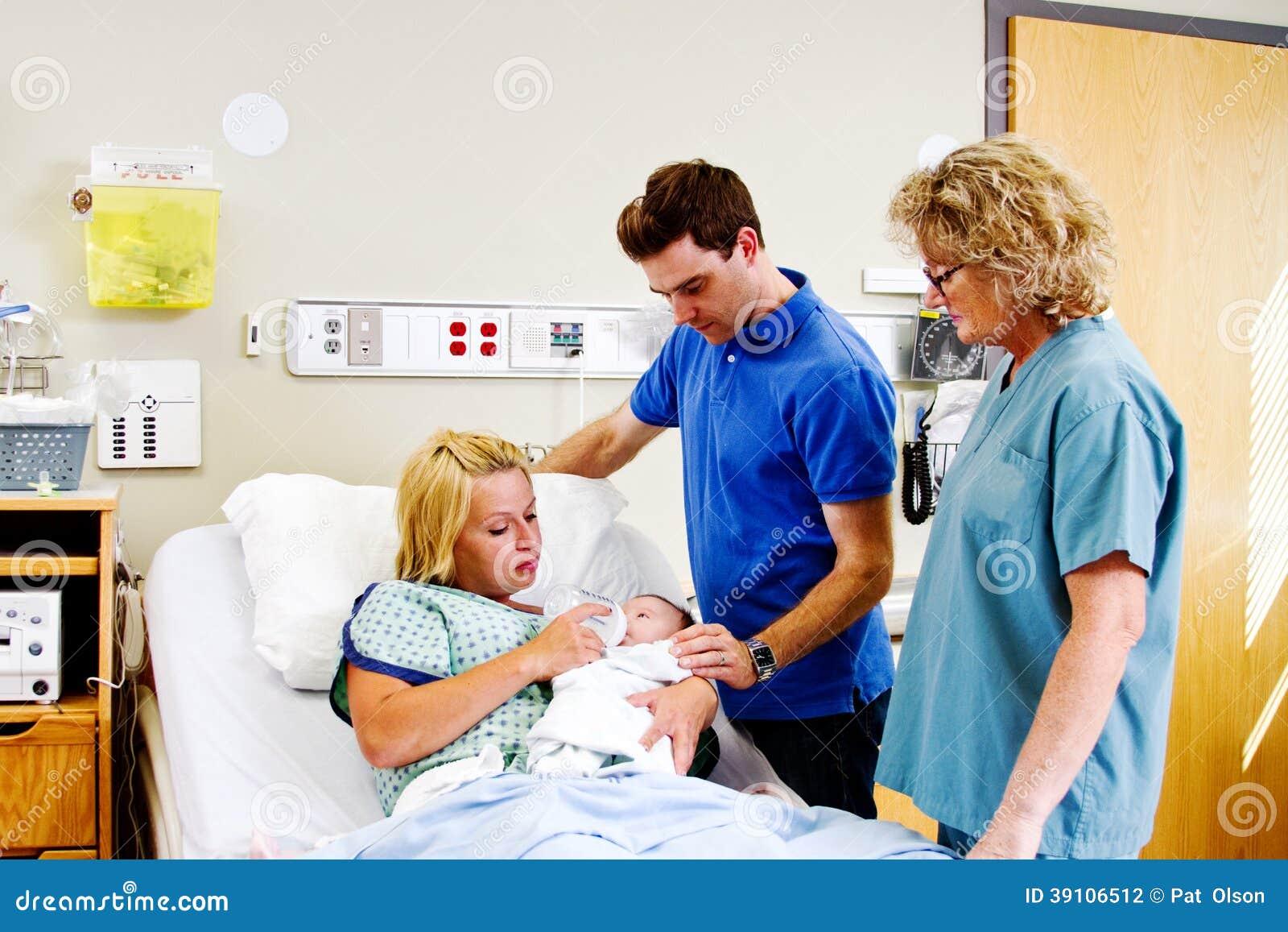 Mamma voedende baby met Papa en verpleegster die kijken