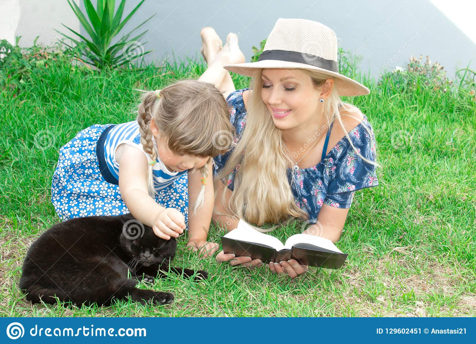 Mammablondinen i en hatt och hennes dotter ligger på gräset och läser en bok, lycklig familj