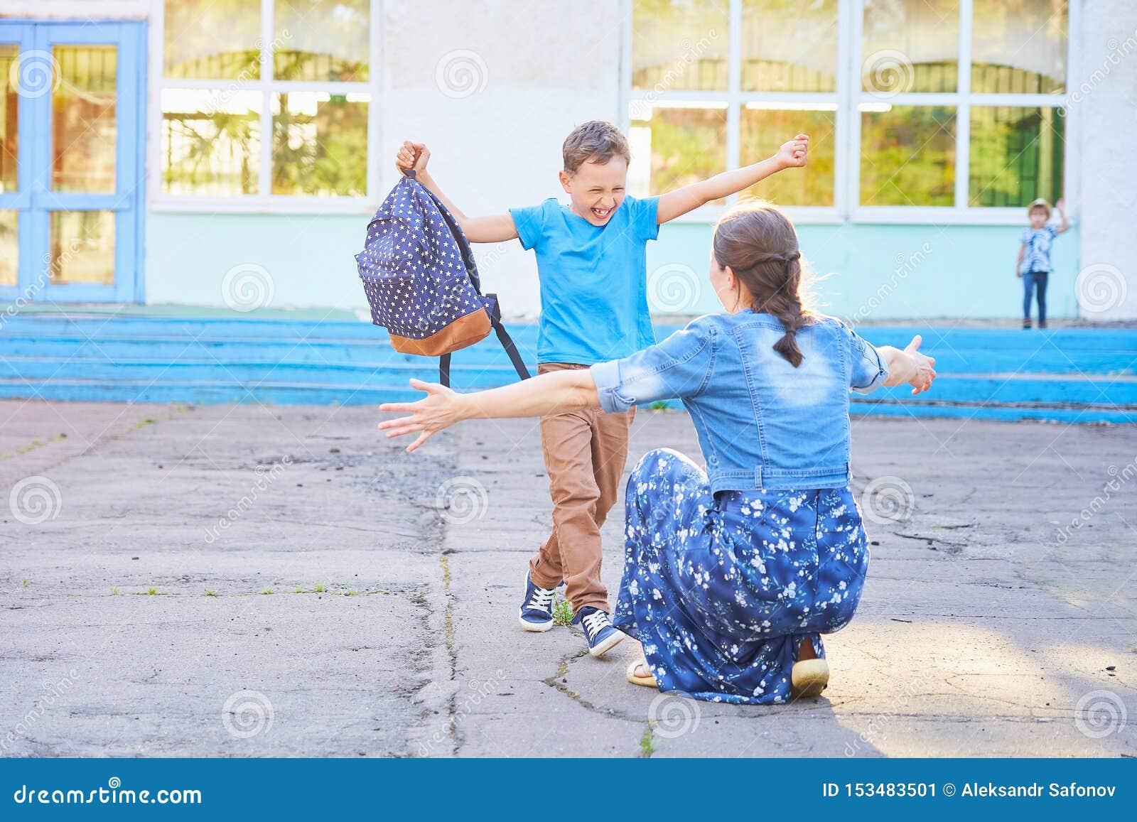 Mamman möter hennes son från grundskolan glade barnkörningar in i armarna av hans moder en lycklig skolpojke kör in mot hans mode