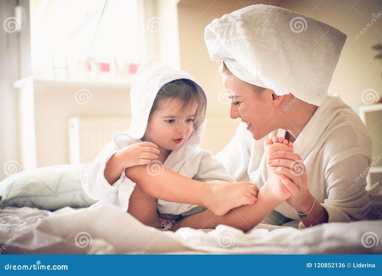 Mamman masserar mig foten Liten flicka med hennes moder efter bad