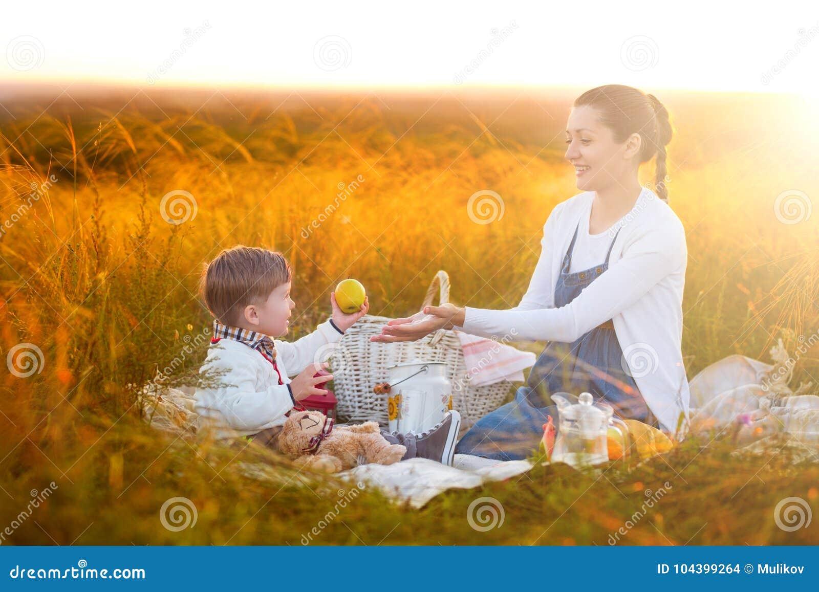 Mamman matar hennes son på en picknick Moder och barnson i solig nedgångdag Lycklig familj och sunt ätabegrepp