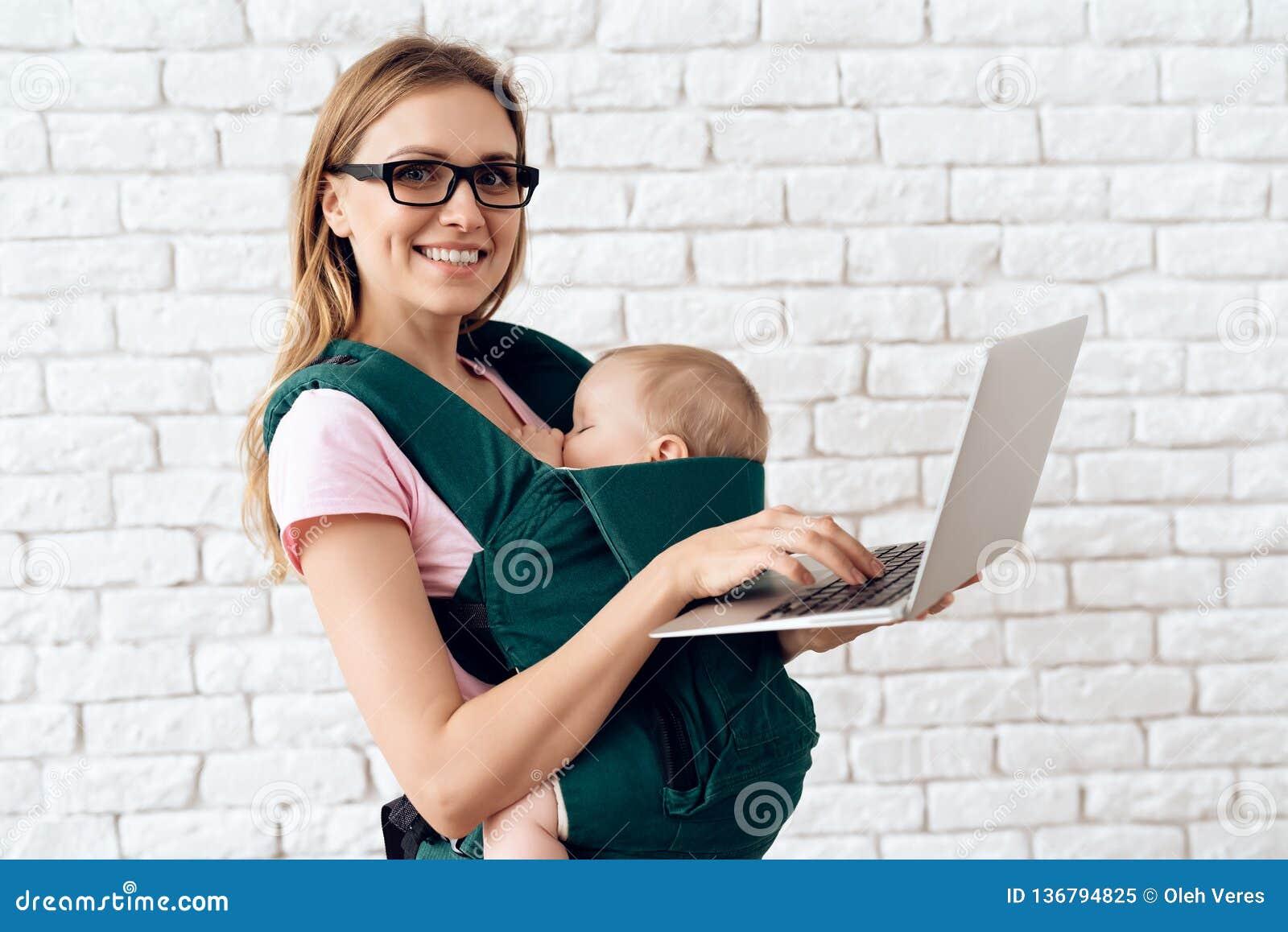 Mamman med den nyfödda bärbara datorn som rymmer behandla som ett barn in, remmen