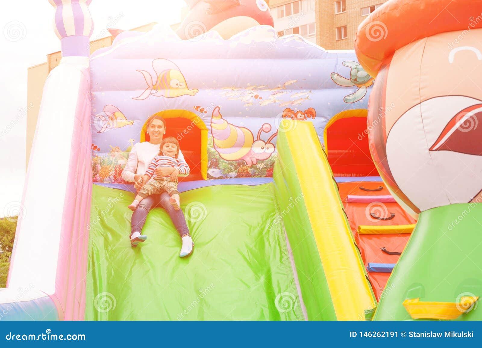 Mamman och barnet rider en glidbana i en uppblåsbar slott