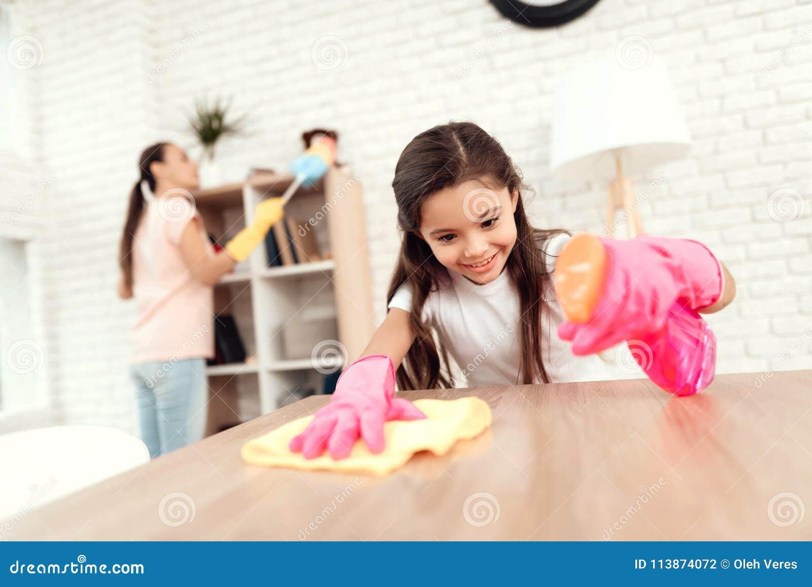 Mamman och dottern gör ren hemma Torka hyllorna och tabellen