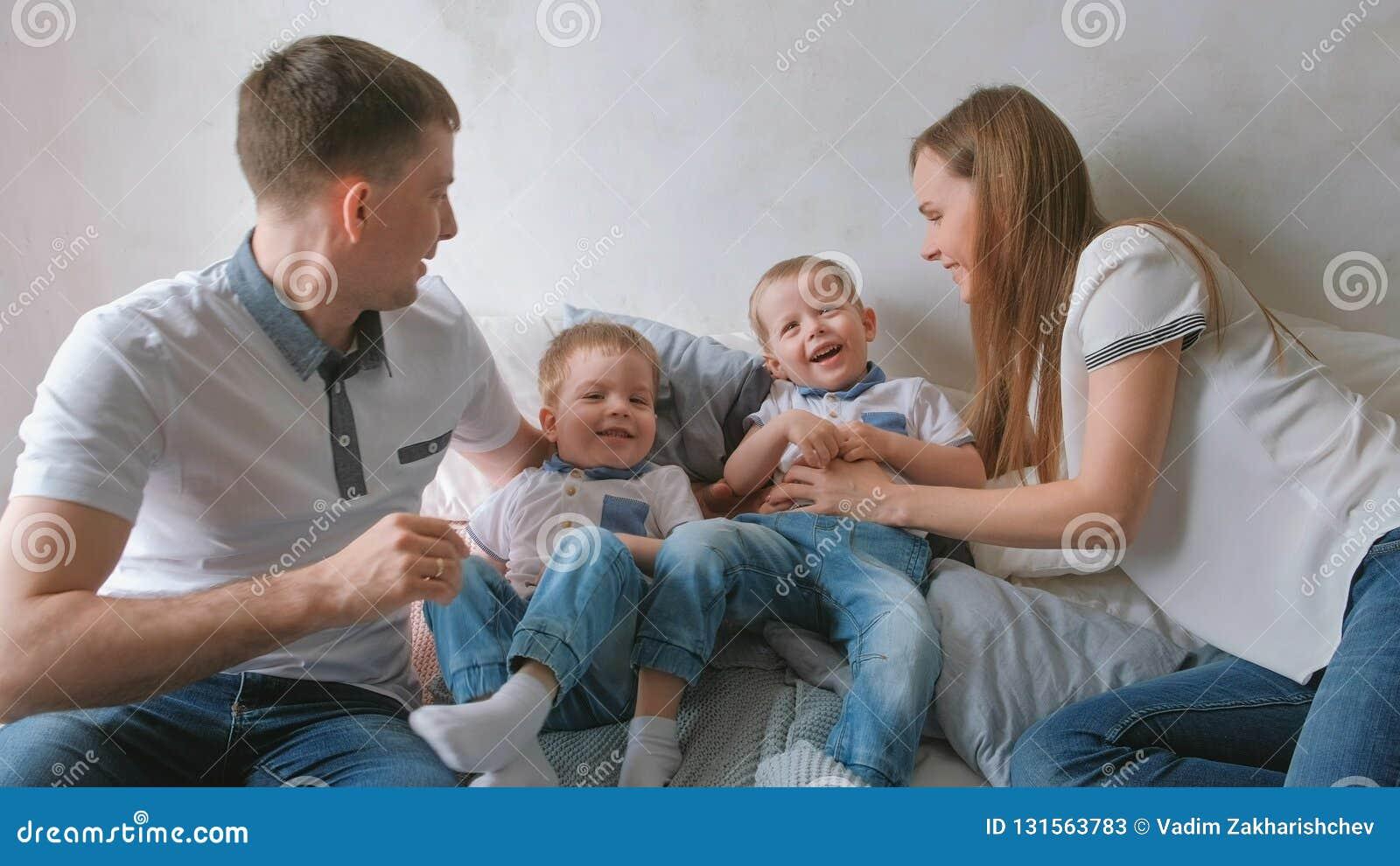 Mamman och farsan spelar med de tvilling- pojkesmå barnen som ligger på sängen Familjfridag