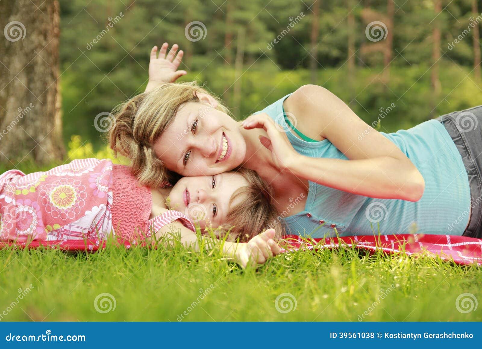 Mamman och hennes lilla dotter ligger på gräset