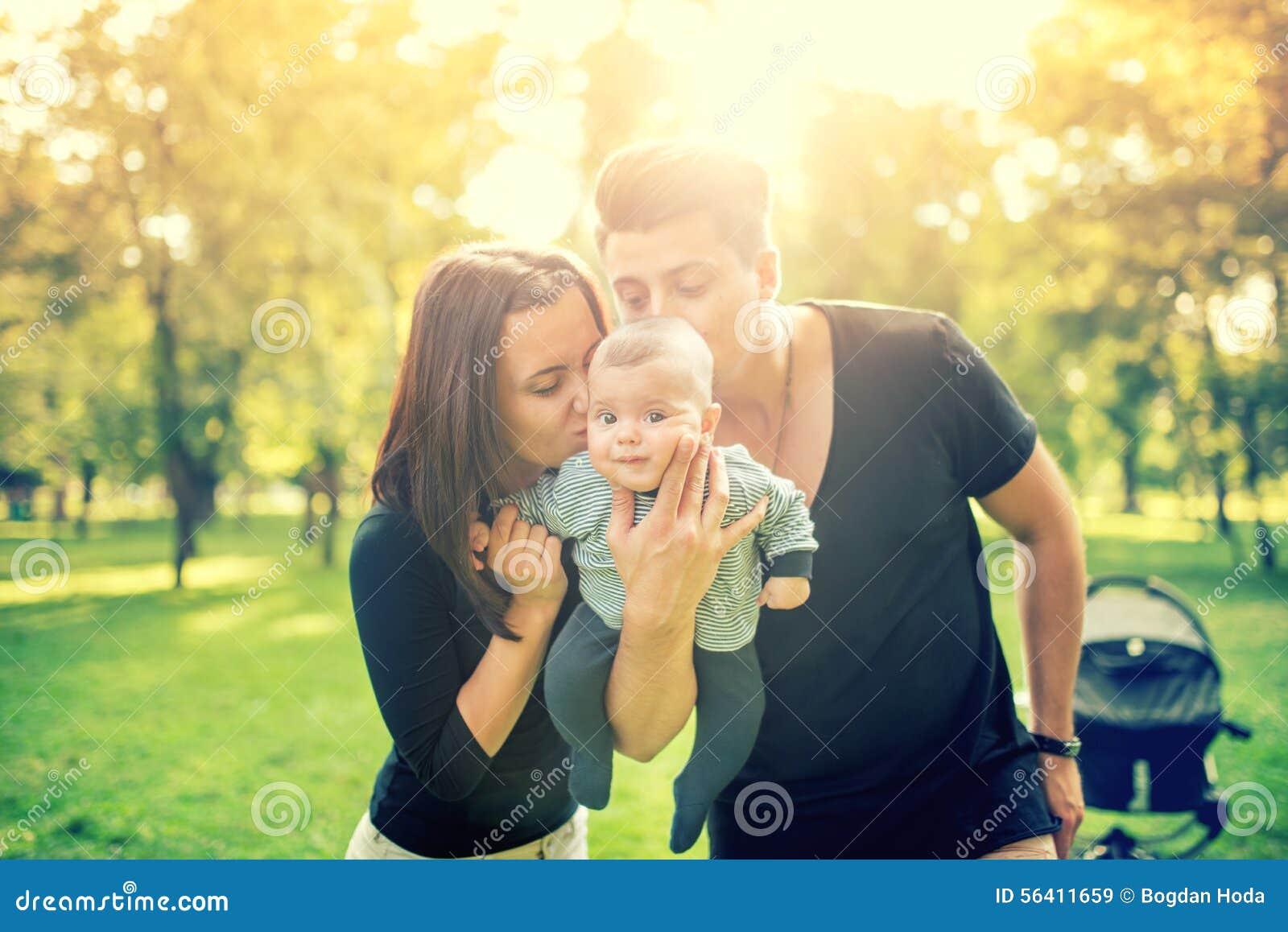 Mamman och pappainnehavet behandla som ett barn, 3 månader gammalt nyfött och att kyssa honom Lycklig familj med fadern, modern o