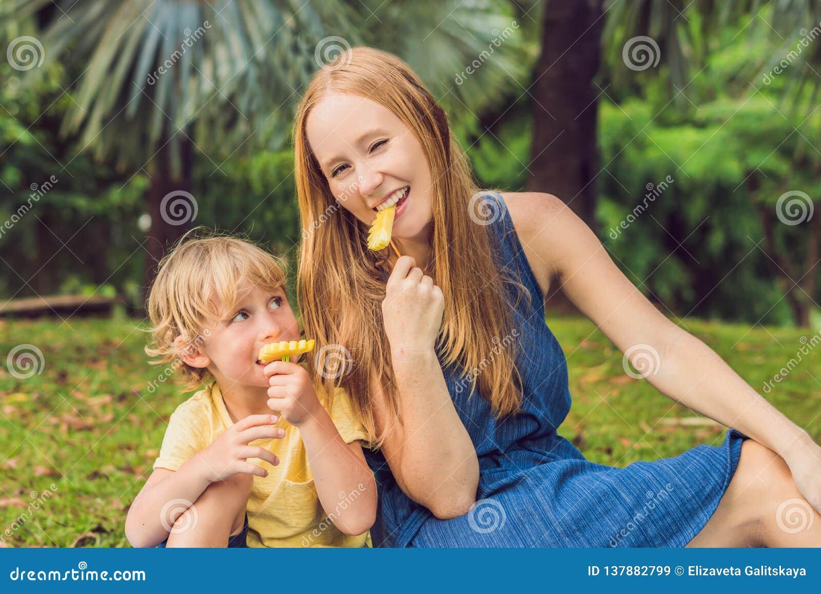 Mamman och sonen hade en picknick i parkera Äta sunda frukter - mango, ananas och melon Barn äter sund mat