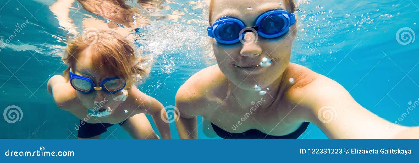 Mamman och sonen, i att dyka exponeringsglas, simmar i pölen under vattenBANRET, långt format
