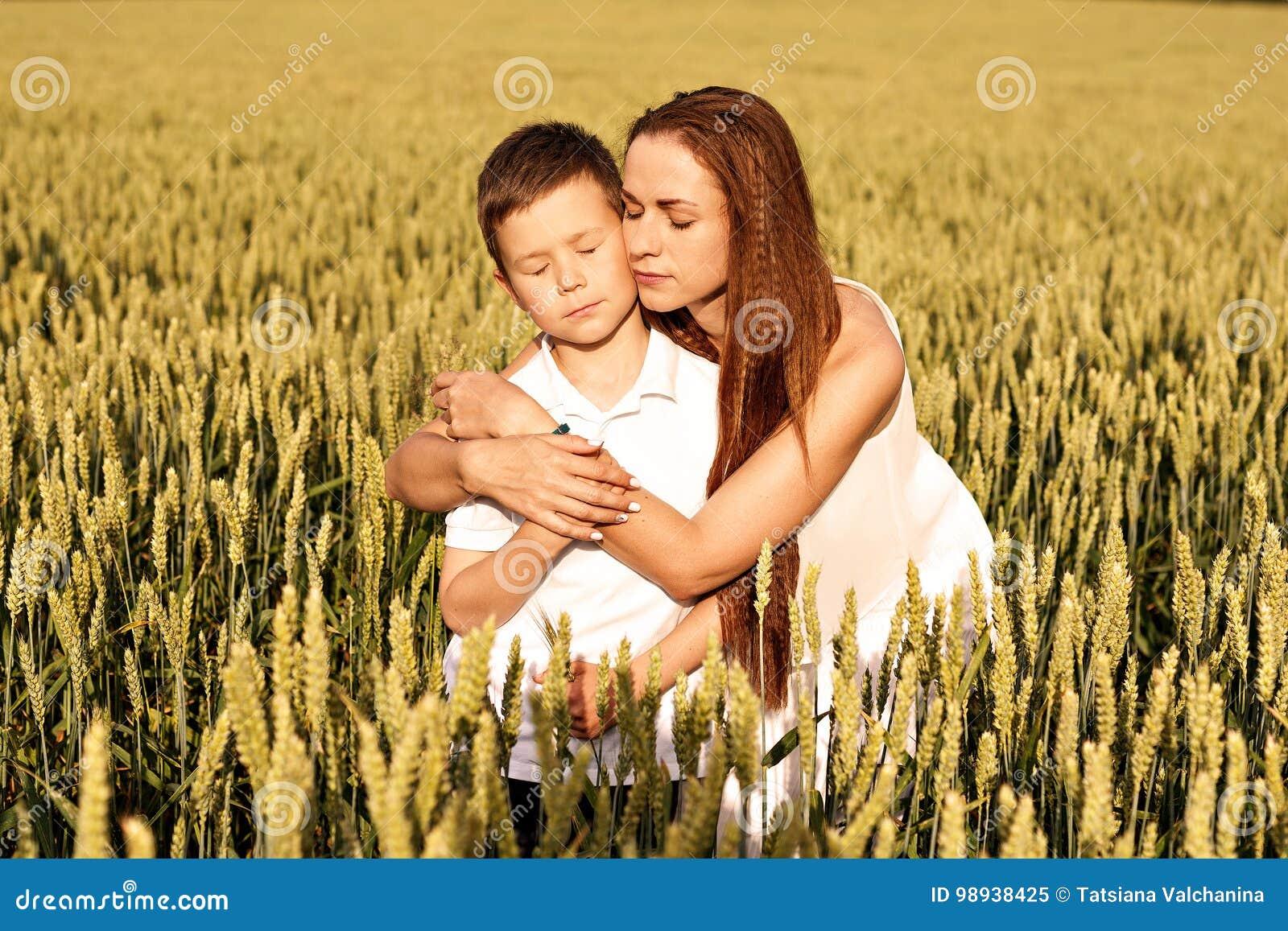 Mamman och sonen kramar i sommaren på ett vetefält