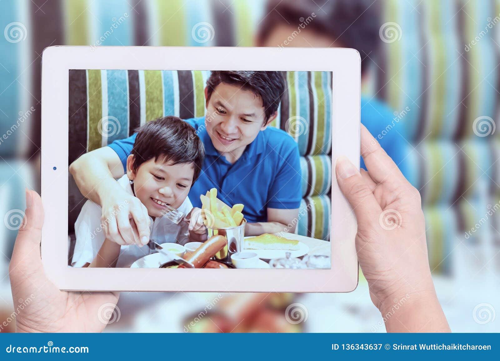 Mamman tar fotoet av den asiatiska pojken och farsan som äter pommes frites