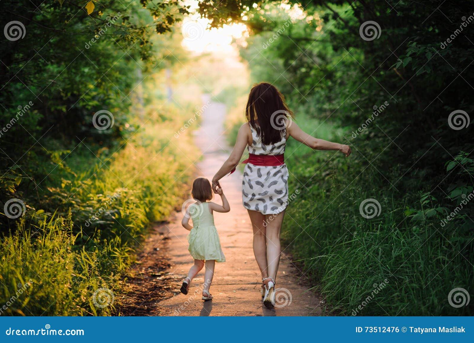 Mammauppehälledotterns hand och går gå på naturen i solnedgångljus