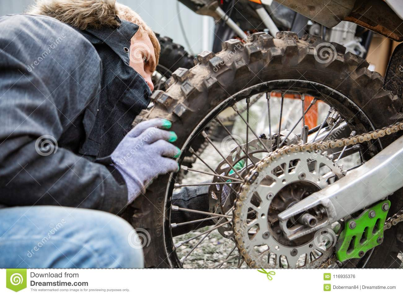 Man Tightens A Wheel To A Motorcycle Close Up Stock Photo