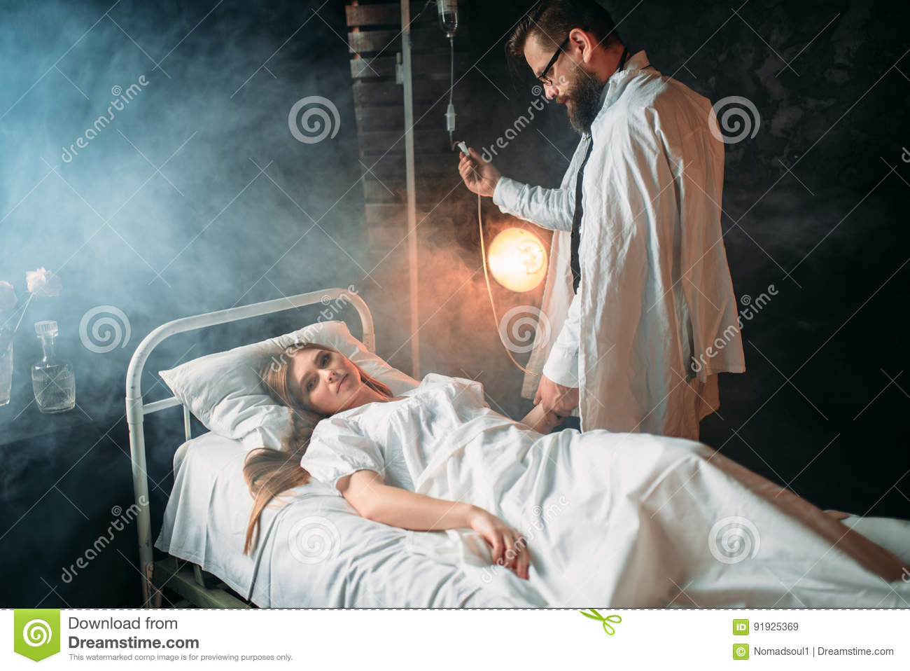 Man Adjusts The Drip Of Sick Woman In The Hospital Stock
