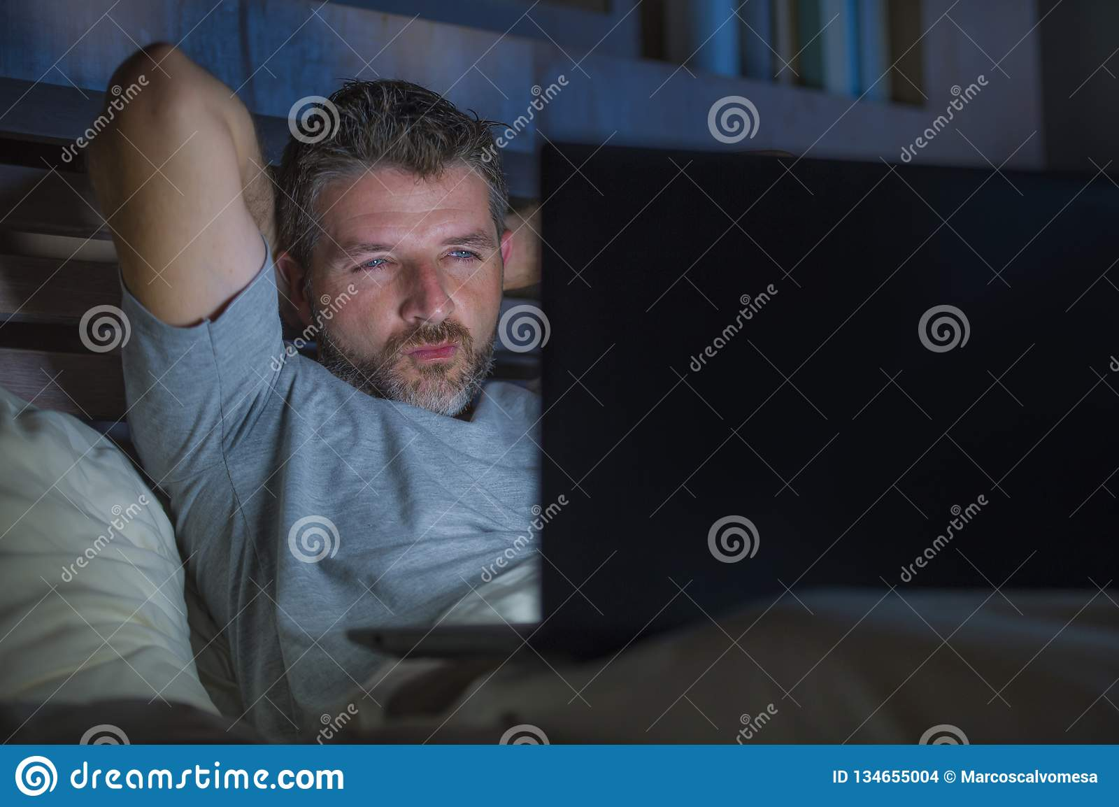 Man alone in bed playing cybersex using laptop computer watching sex movie late at night with lascivious pervert face