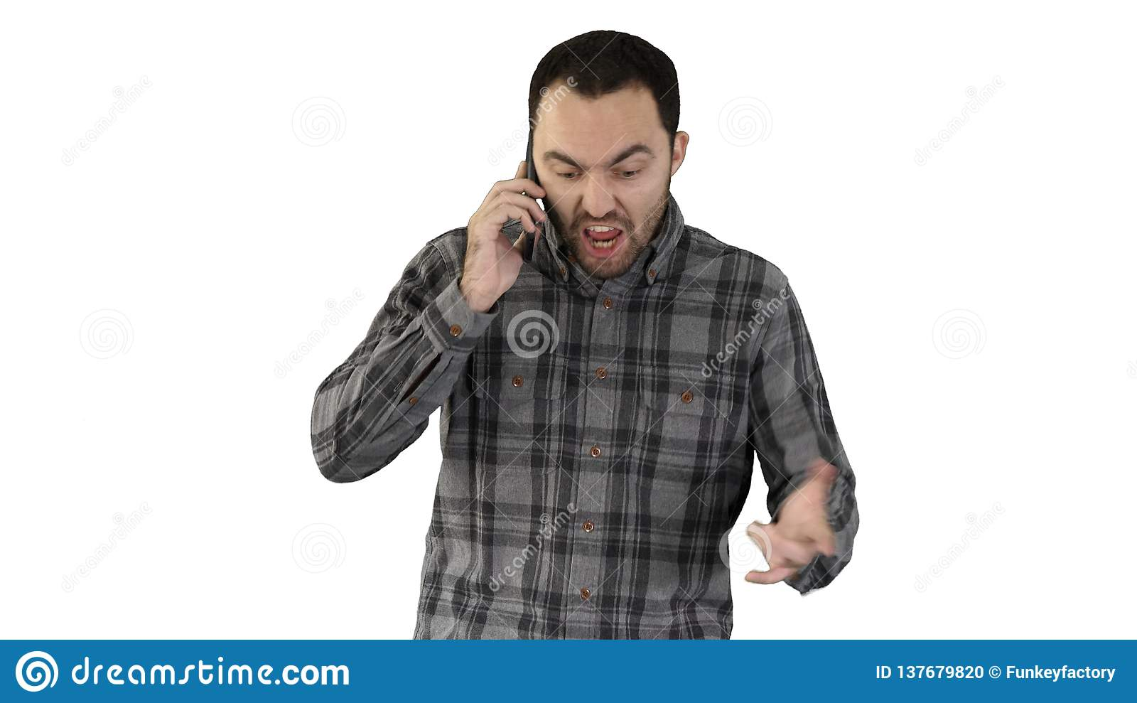 Man angry talking on telephone and walking on white background.