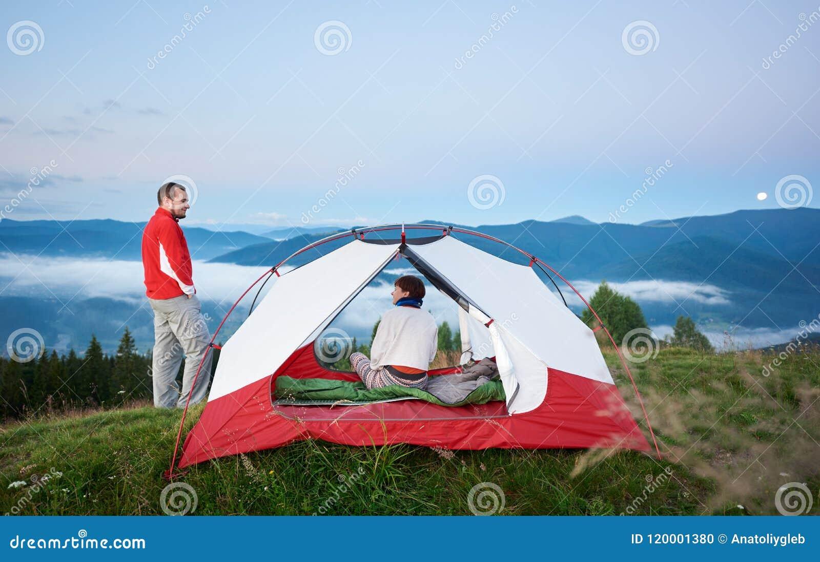 Man anseendet nära tältet som sitter i kvinnan mot härligt landskap av väldiga berg