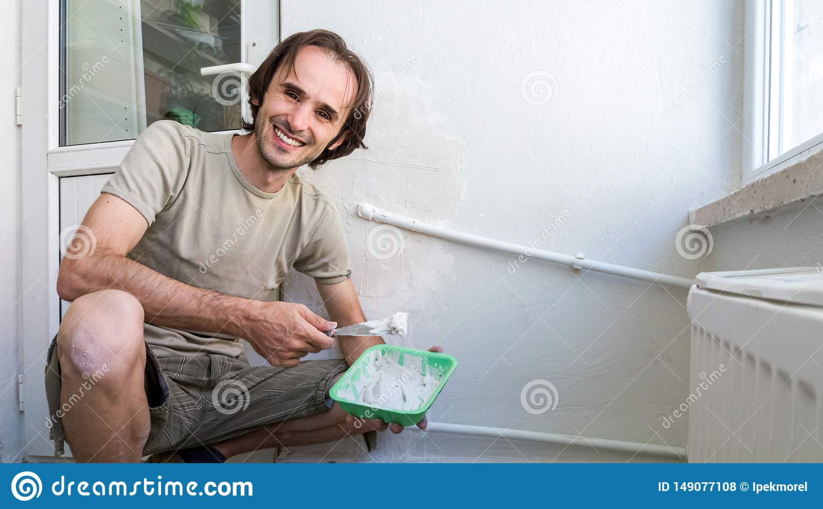 Man applying plaster mix on the wall with spatula. Easy home renovating concept.