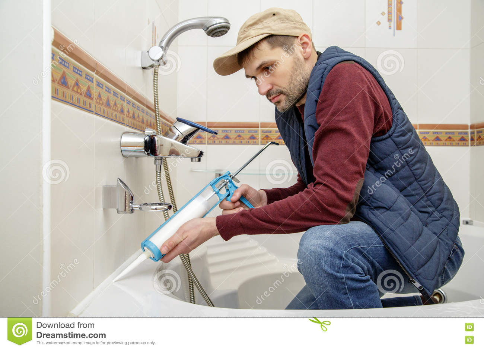 Man applying silicone sealant in the bathroom stock photo for Bathroom caulking service
