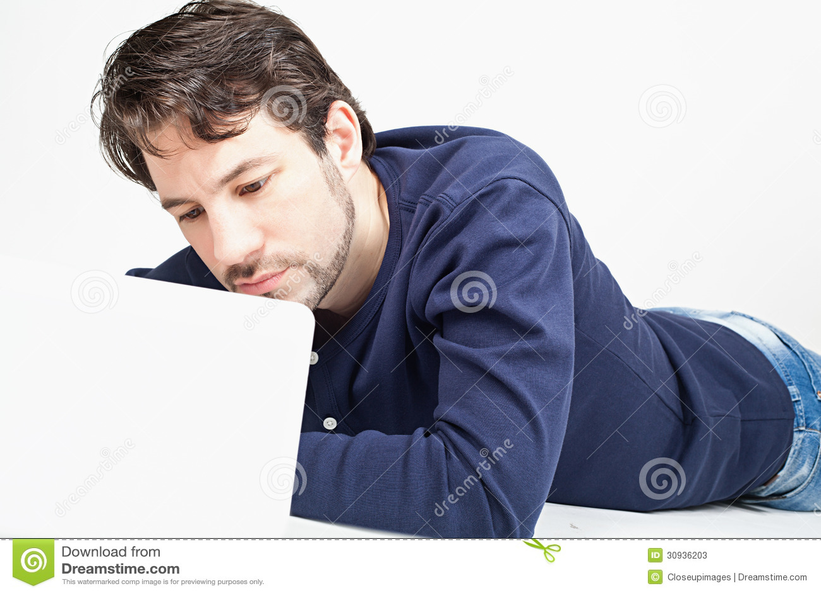 Man arbete på bärbara datorn, medan lägga på golvet