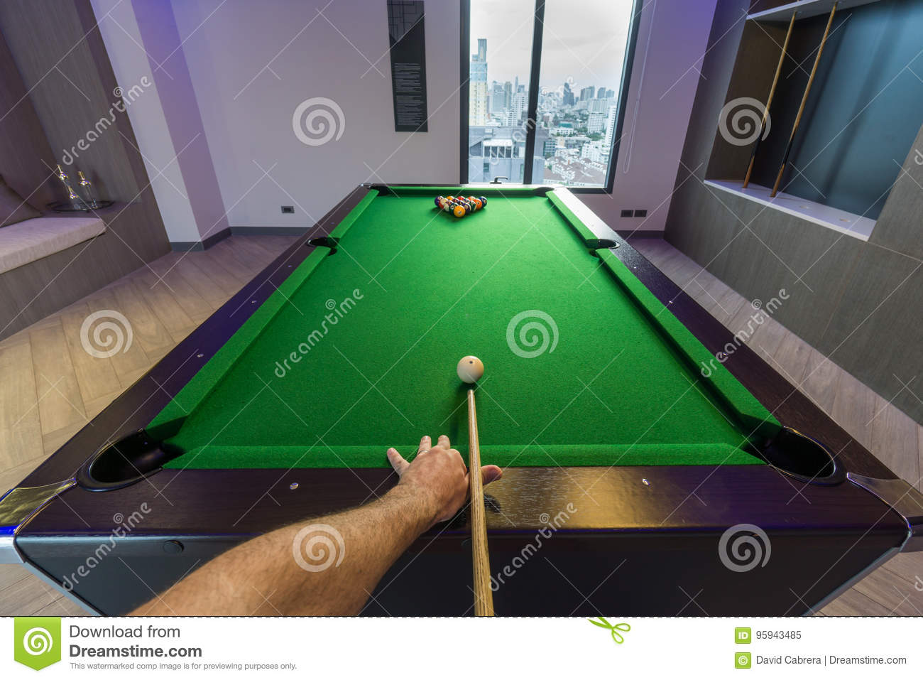 Man arm playing Snooker Pool green table in a modern games room