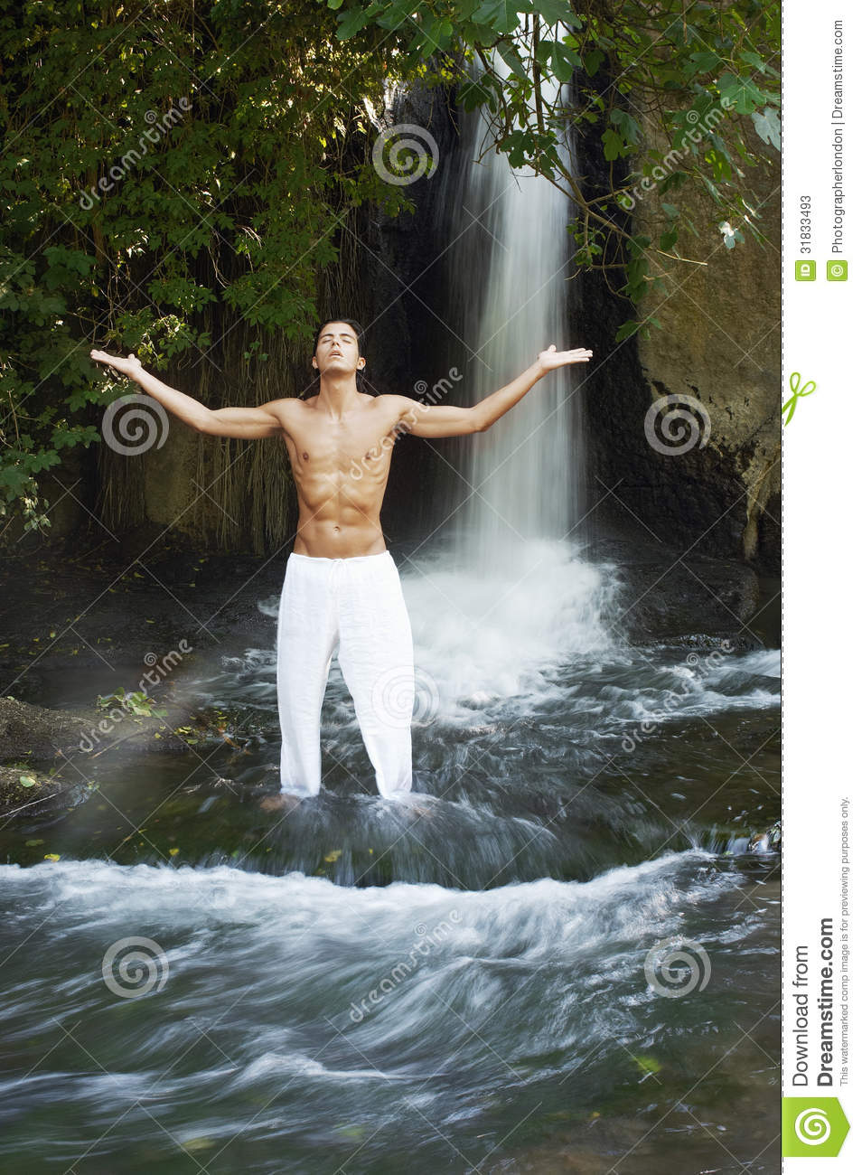 Man With Arms Outstretched Meditating Against Waterfall